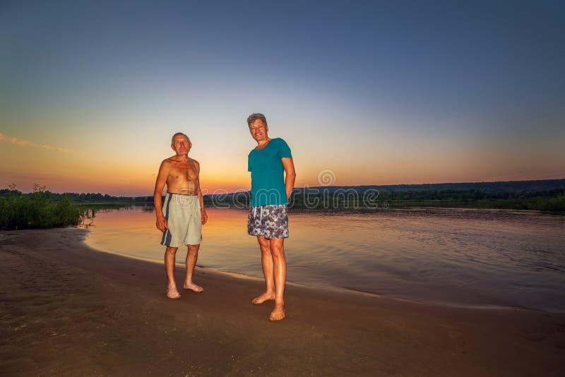 Dois companheiros em uma praia selvagem do rio contra o contexto de um por do sol imagens de stock royalty free