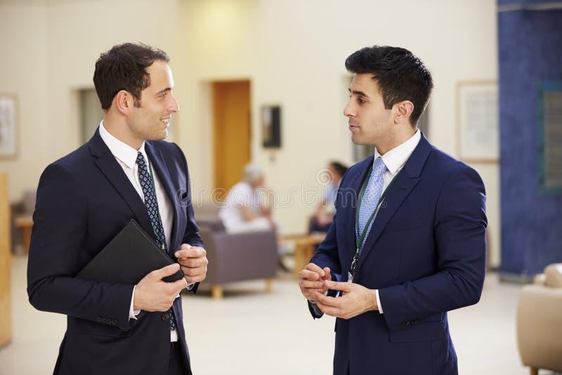Dois consultantes que têm a reunião na recepção do hospital fotografia de stock