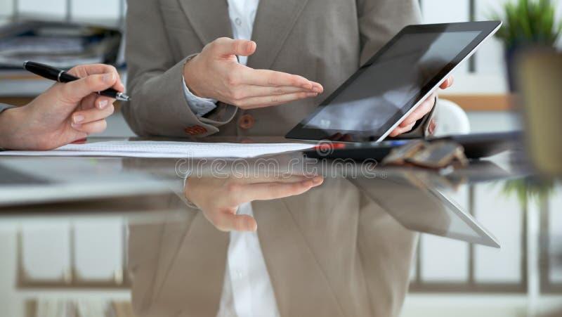 Dois contadores fêmeas que usam a tabuleta ao verificar o balanço financeiro ou ao contar a renda para o formulário de imposto, c fotos de stock