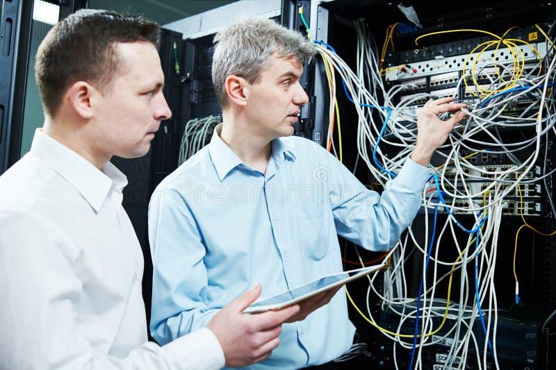 Dois coordenadores de apoio da rede que administram na sala do servidor imagens de stock
