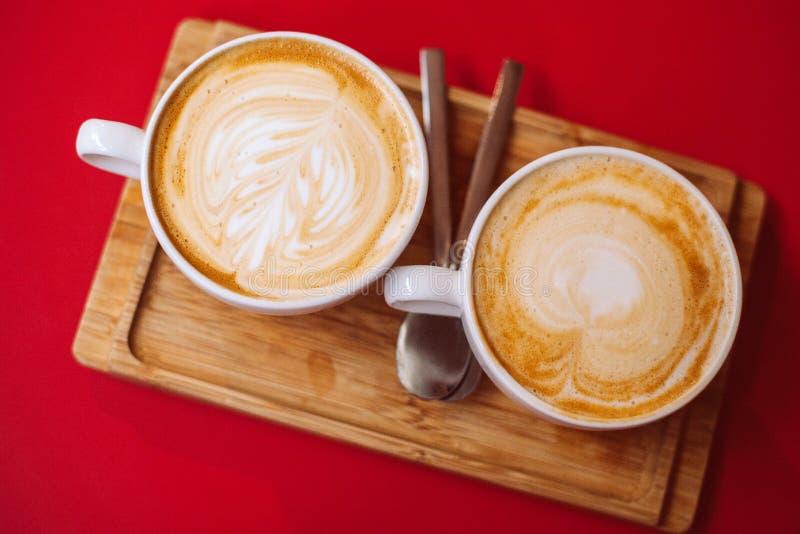 Dois copos brancos do café quente do latte do café do cappuccino na tabela vermelha no café fotos de stock royalty free