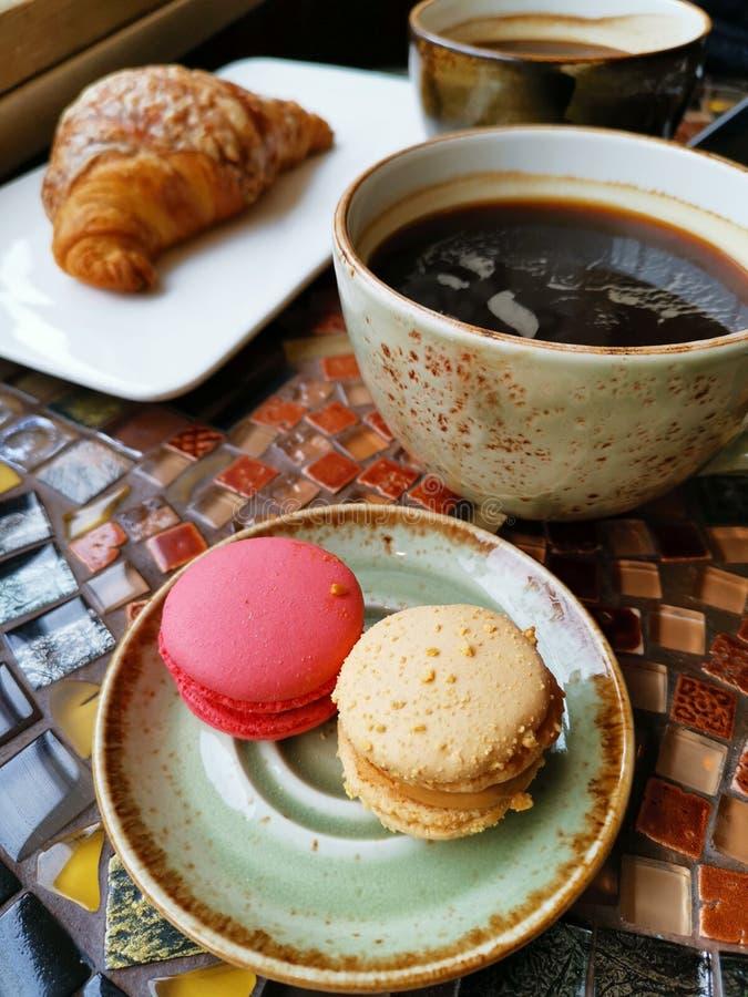 Dois copos cerâmicos do café preto com croissant e bolos do macarrão em uma tabela do vintage foto de stock royalty free