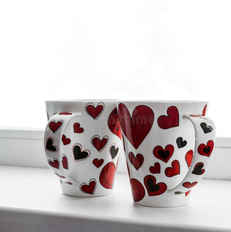 Dois copos com corações na tela isolada no fundo branco foto de stock royalty free