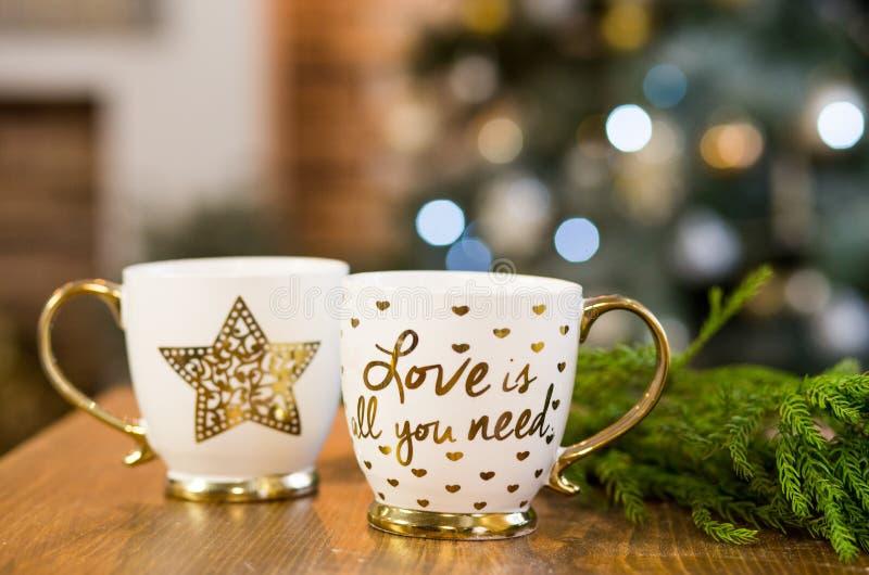 Dois copos com texto no Natal interior com luzes no fundo imagens de stock