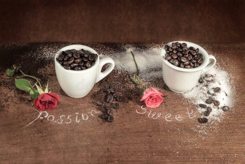Dois copos completos de feijões de café com botão vermelho aumentaram na tabela de madeira fotografia de stock royalty free