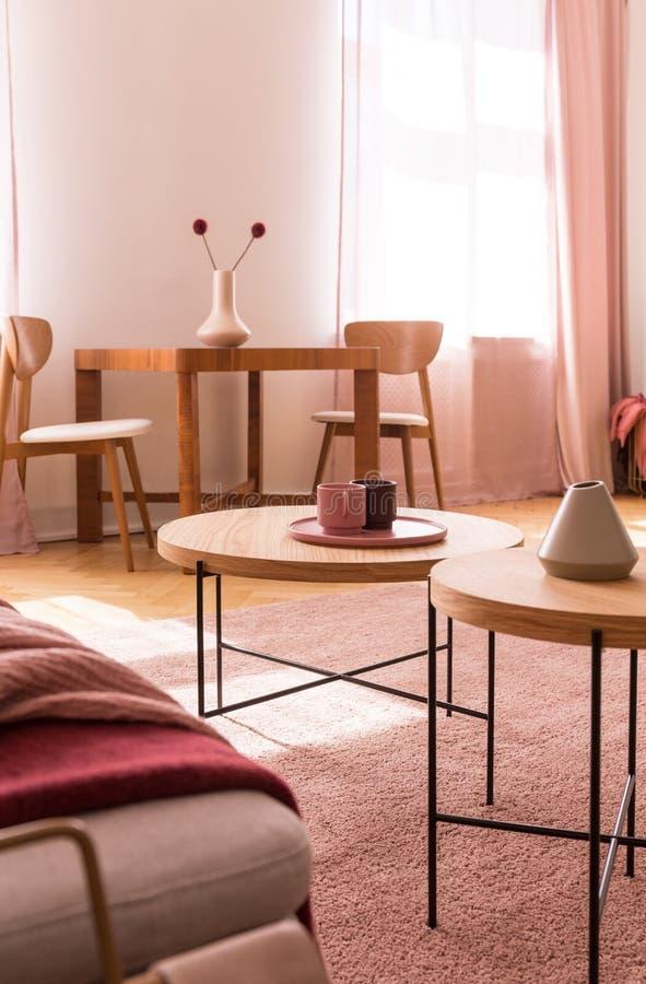 Dois copos de café e vaso bege pequeno em mesas de centro de madeira na sala de visitas cor-de-rosa pastel elegante foto de stock