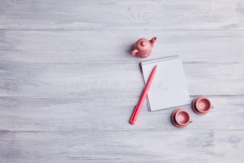 Dois copos de chá cor-de-rosa pequenos com chaleira em um fundo de madeira Cartão com um caderno e uma pena imagens de stock royalty free