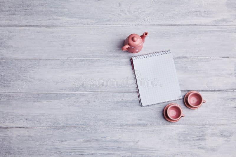 Dois copos de chá pequenos com uma chaleira cor-de-rosa e um caderno em um fundo de madeira foto de stock royalty free