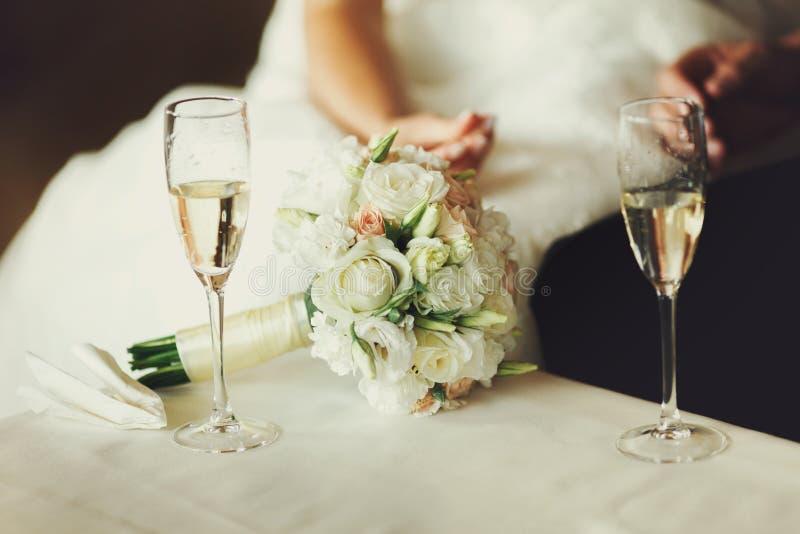 Dois copos de vinho com champanhe estão na tabela atrás de um weddi imagem de stock