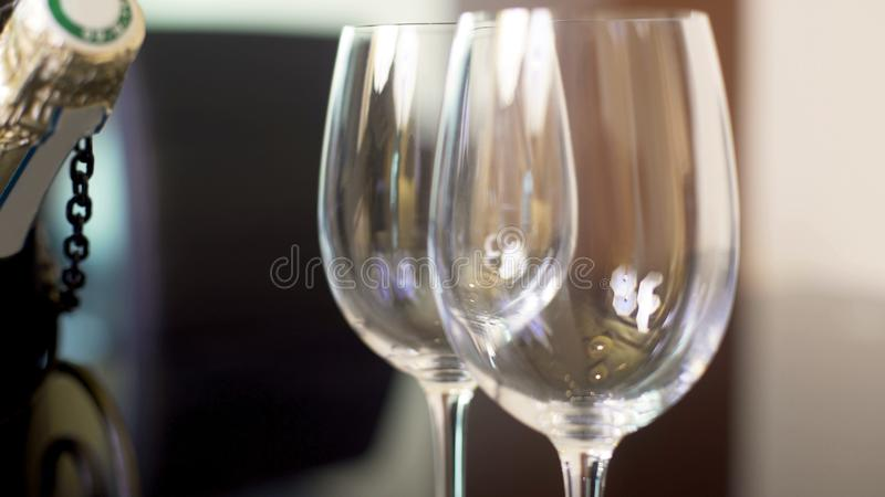 Dois copos de vinho e posições vazios na tabela, celebração da garrafa do champanhe imagens de stock