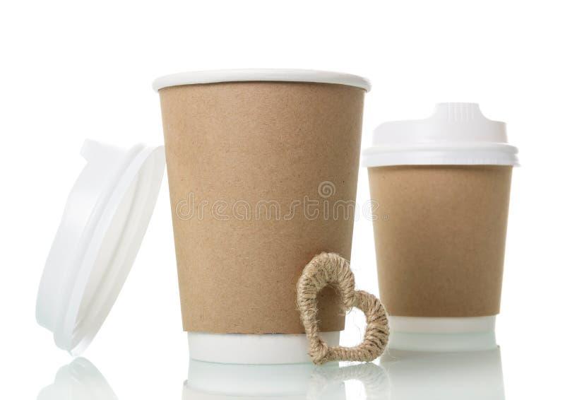 Dois copos do único-uso para o café a levar embora e o coração pequeno, isolados no branco fotos de stock royalty free