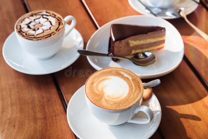 Dois copos do café do cappuccino e da musse de chocolate quentes endurecem fotografia de stock