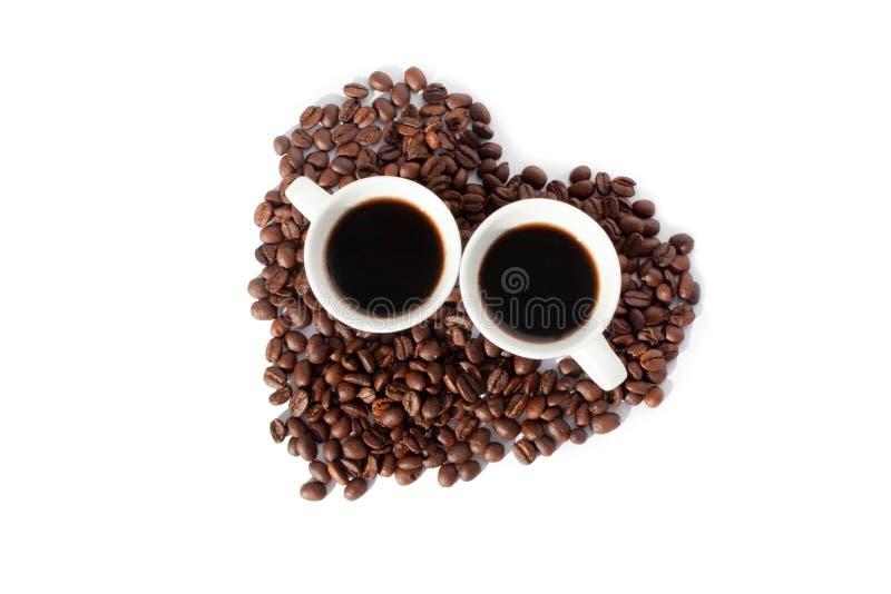 Dois copos do caf? preto e de um cora??o feito de feij?es de caf? backgroung branco na vista superior isolada foto de stock royalty free