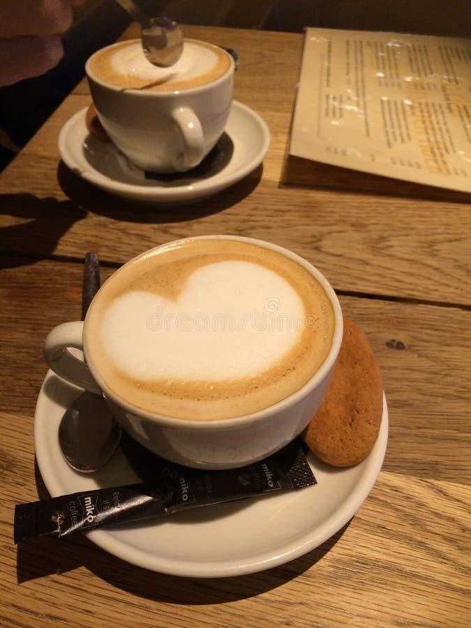 Dois copos do cappuccino em uma tabela de madeira com cora??o espumoso e um biscoito imagens de stock