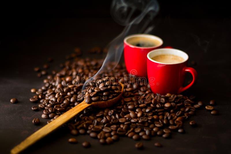 Dois copos vermelhos do café com os feijões de café no fundo de madeira escuro fotografia de stock royalty free