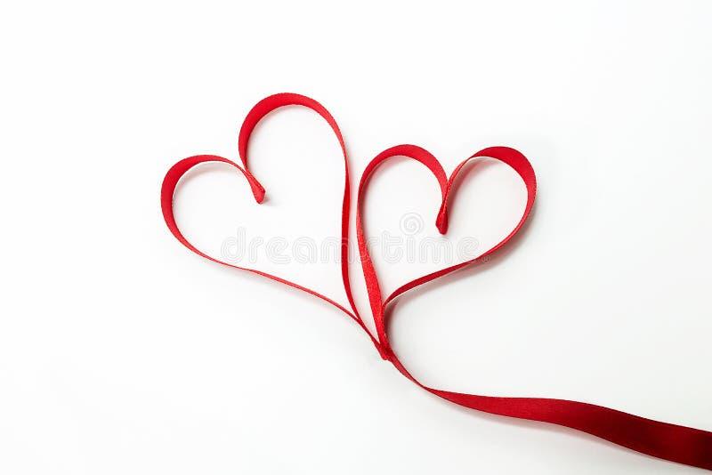 Dois corações amarrados junto fizeram da fita vermelha fotografia de stock royalty free