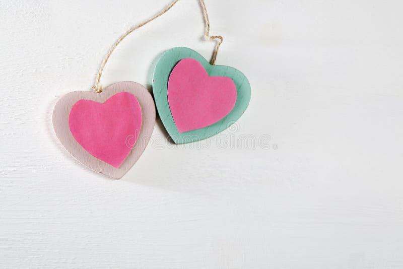 Dois corações de madeira penduram em uma parede de madeira branca foto de stock royalty free