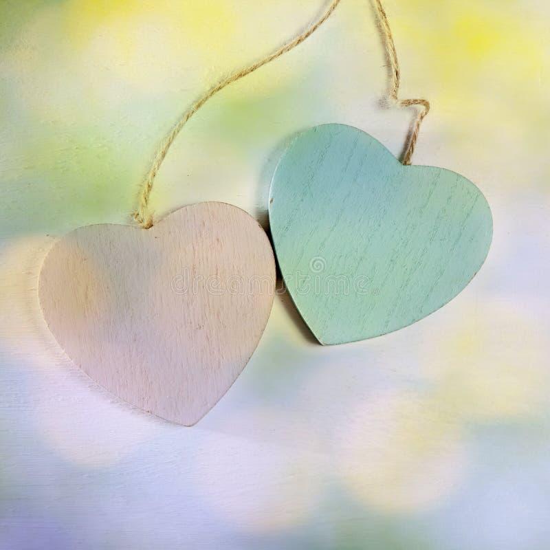 Dois corações de madeira penduram em uma parede de madeira branca imagem de stock royalty free