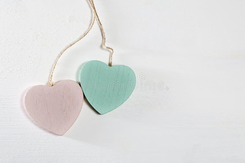 Dois corações de madeira penduram em uma parede de madeira branca foto de stock