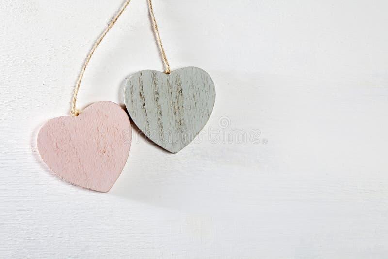 Dois corações de madeira penduram em uma parede de madeira branca imagens de stock royalty free
