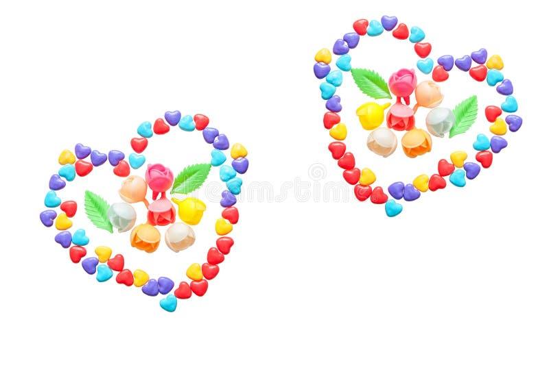 Dois corações de poucos corações coloridos dos doces Flores caramelizadas Isolado em um fundo branco imagem de stock royalty free