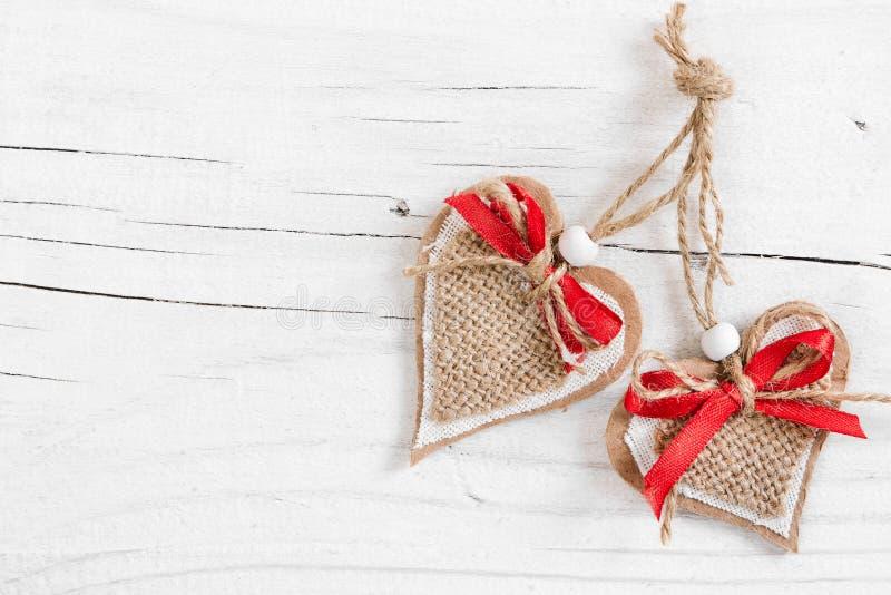 Dois corações decorativos no fundo branco de madeira fotos de stock royalty free