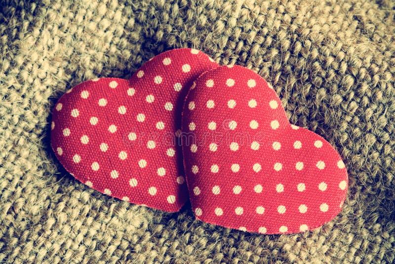 Dois corações decorativos no fundo do pano de saco fotografia de stock