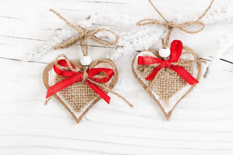 Dois corações decorativos no ramo coberto de neve fotos de stock