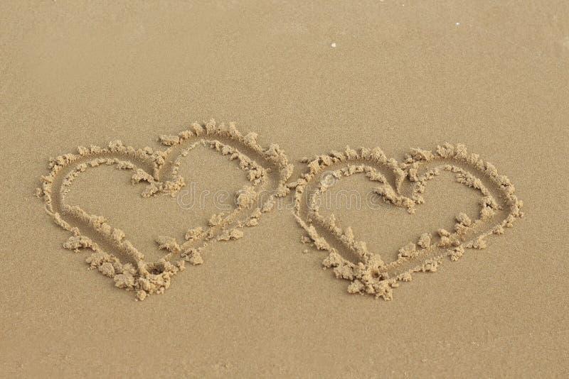 Dois corações desenhados na areia na praia imagens de stock
