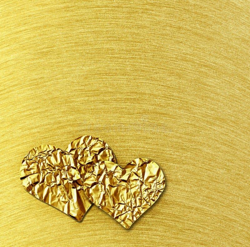 Dois corações do ouro no fundo escovado aço do ouro imagens de stock