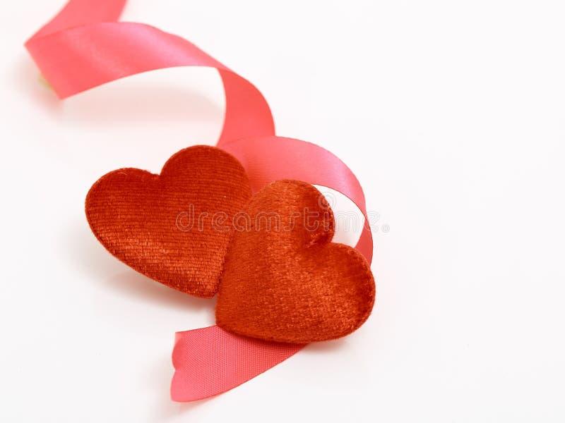 Dois corações e fita vermelha imagem de stock