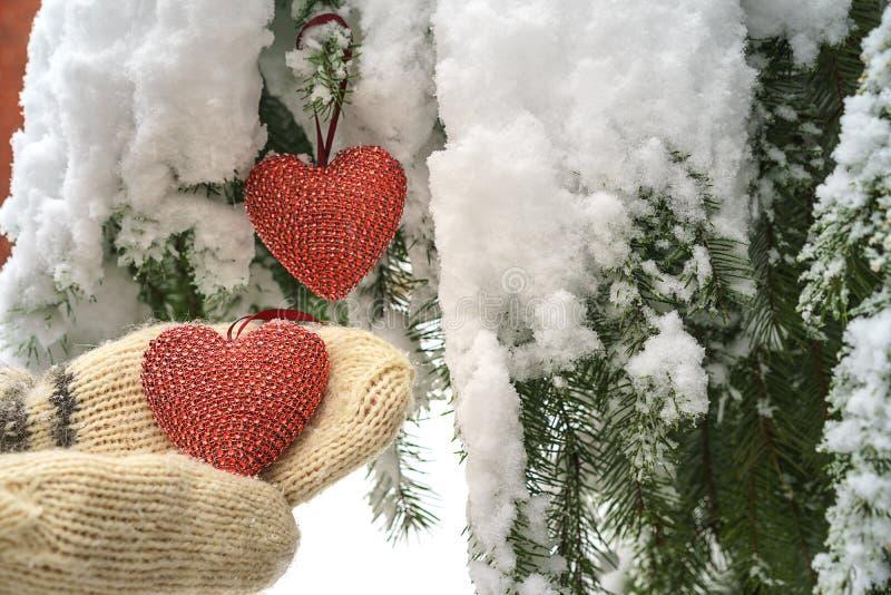 Dois corações e mãos vermelhos de matéria têxtil no fundo nevado pesado do ramo do abeto, perto da casa do tijolo vermelho Feliz  imagens de stock royalty free