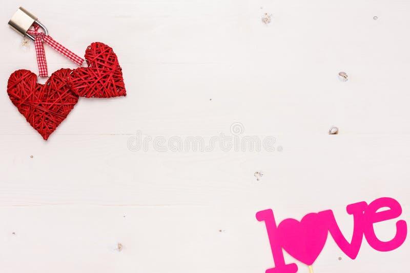 Dois corações fechados e o amor da palavra em um fundo de madeira imagens de stock royalty free