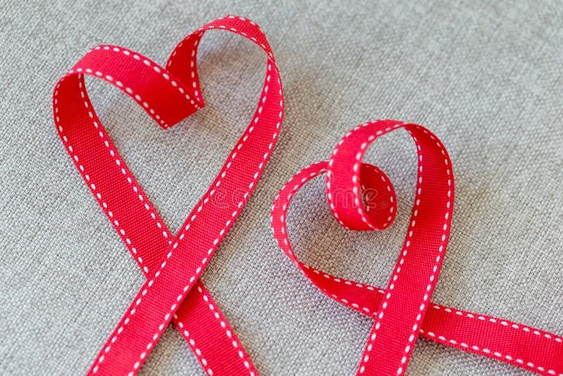 Dois corações feitos da fita vermelha na matéria têxtil de linho foto de stock