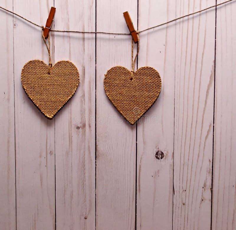 Dois corações marrons de pano penduraram na frente de uma cerca de madeira imagens de stock