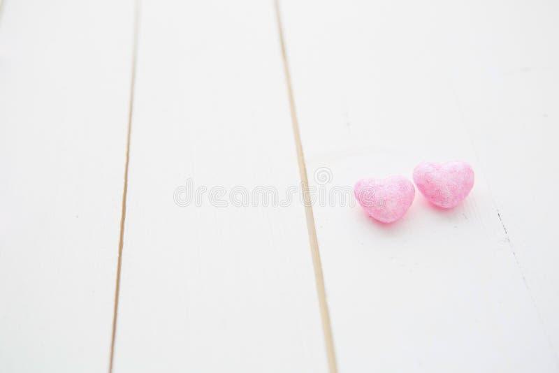 Dois corações que penduram no fundo de madeira pintado branco foto de stock royalty free