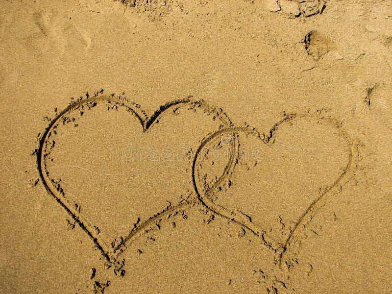Dois corações tirados na areia de uma praia imagens de stock royalty free