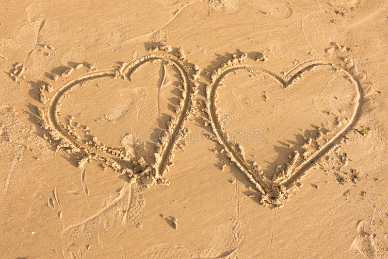 Dois corações tirados na areia no mar encalham foto de stock royalty free