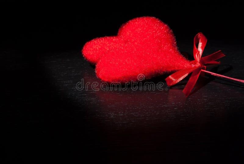 Dois corações vermelhos de veludo decorativo na luz escura preta e na tabela de madeira, conceito do dia de são valentim foto de stock