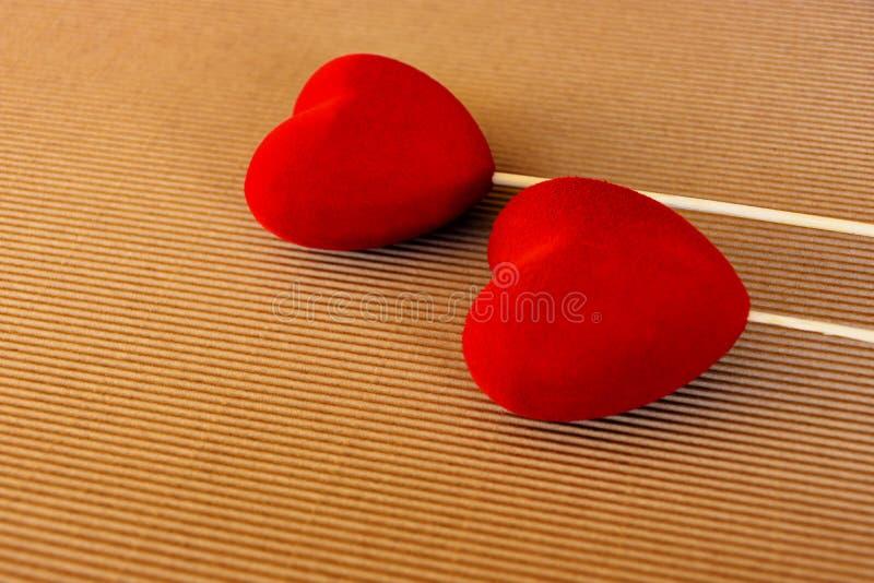 Dois corações vermelhos de veludo em uma superfície marrom natural do cartão Cartão dos cumprimentos do dia de Valentim do St Dia fotografia de stock