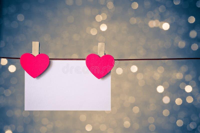 Dois corações vermelhos decorativos com o cartão que pendura no fundo claro azul e dourado do bokeh, conceito do dia de são valent imagem de stock royalty free