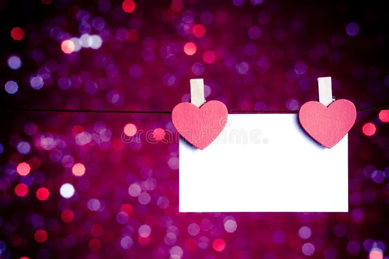 Dois corações vermelhos decorativos com o cartão que pendura no fundo claro azul e violeta do bokeh, conceito do dia de são valent fotografia de stock royalty free