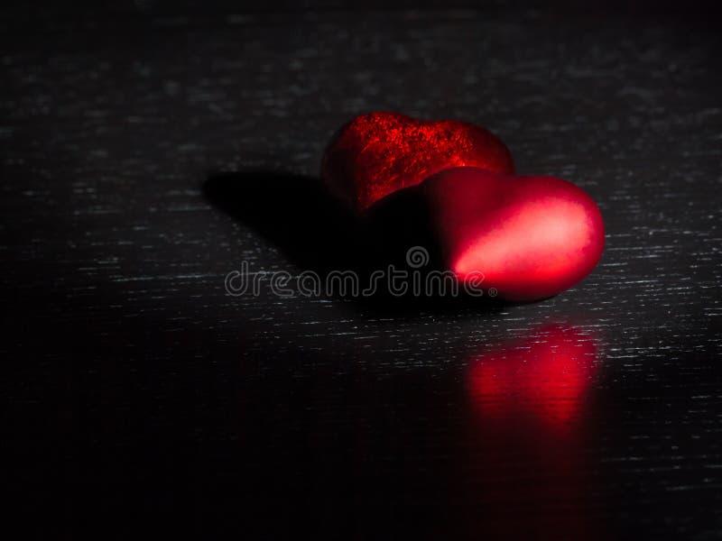 Dois corações vermelhos decorativos na luz escura preta e na tabela de madeira, conceito do dia de são valentim fotografia de stock