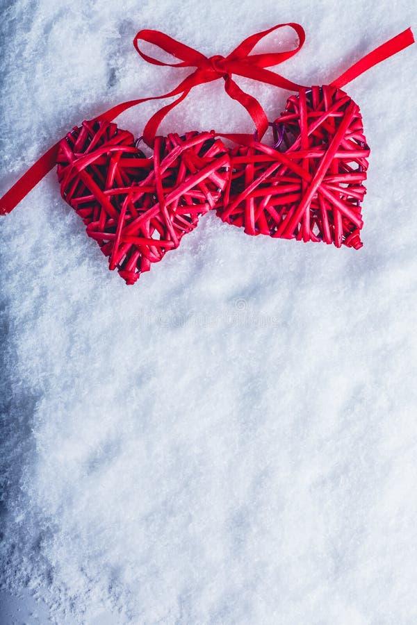 Dois corações vermelhos do vintage bonito amarrados junto com uma fita em um fundo branco da neve Amor e conceito do dia de Valen fotos de stock