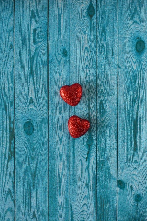 Dois corações vermelhos em um fundo azul com textura de madeira fotografia de stock