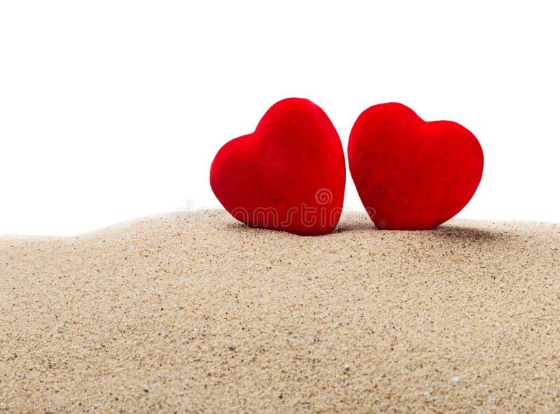 Dois corações vermelhos na areia em um branco foto de stock royalty free