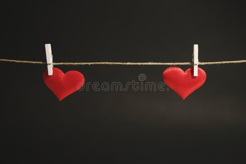 Dois corações vermelhos que penduram distante de uma corda pelo Peg de roupa branco O dia ou a ocasião romântica de Valentim com  fotos de stock royalty free