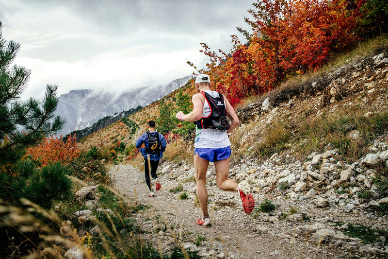 Dois corredores dos atletas que correm da montanha ao longo da fuga na paisagem do outono imagens de stock