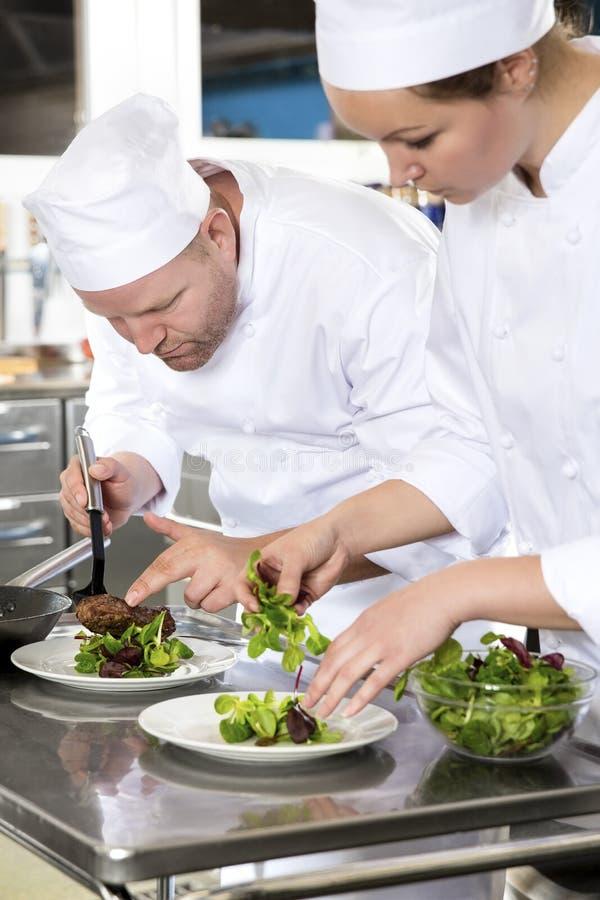Dois cozinheiros chefe dedicados preparam o prato do bife no restaurante gourmet fotos de stock