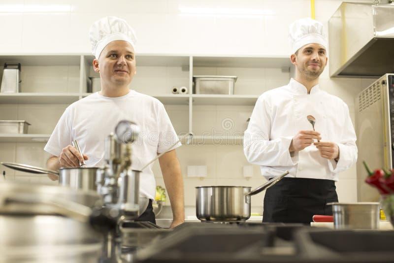 Dois cozinheiros chefe do cozinheiro na cozinha profissional foto de stock